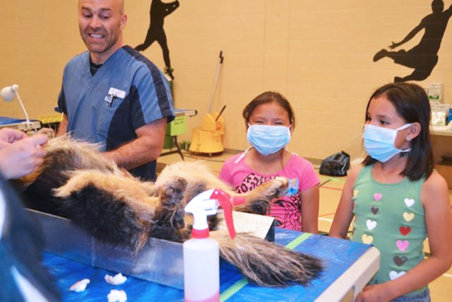 Local children watch a canine surgery during the CAP spay-neuter clinic at Little Pine First Nation in May 2014.